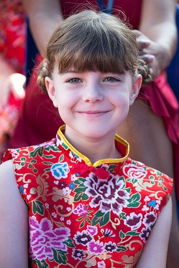 A kid is wearing a Chinese traditional dress on the day of Harrovian Chinese new year celebrations