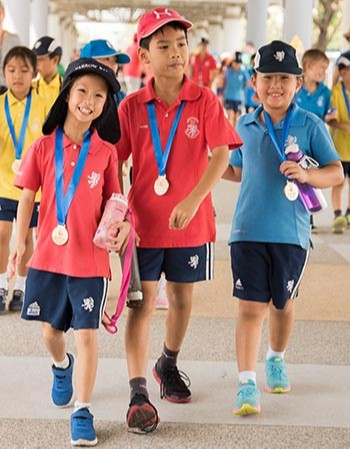 Pre prep students at harrow Bangkok walking the way with medals
