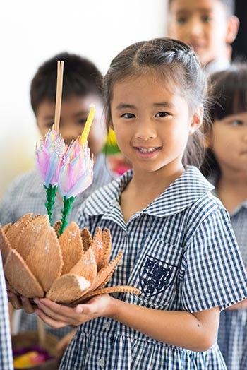 A kid holding krathong on the day of Loi Krathong festival celebrations