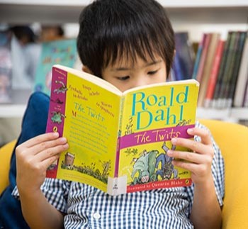 A kid is reading Roald Dahl book at Harrow Bangkok library