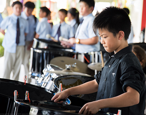 A kid playing drums at an event