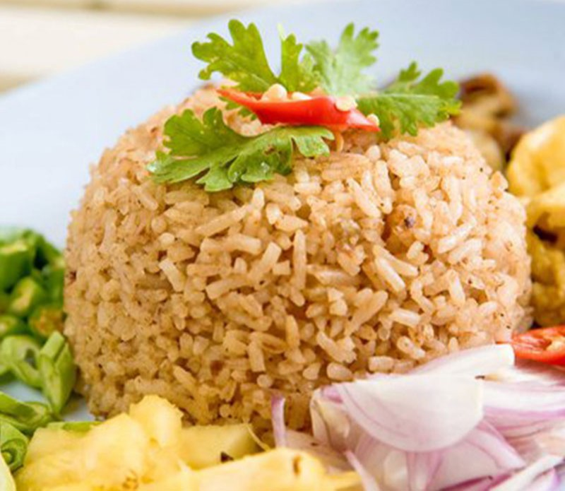 Rice garnished with coriander and red chili with lots of toppings like beans, onions, lemon